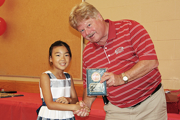 Emily Chen of the Dolphins Swim Team of Burlington recieves an award for best in 7 and under age group