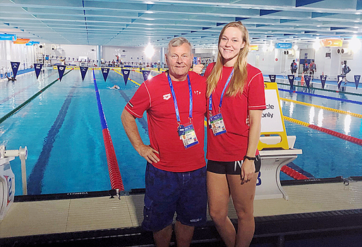 Kristina Steins of the Dolphins Swim Team of Burlington stands beside her coach, Cecil Russel in front of the pool at the 2019 Fina World Championships